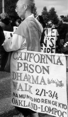A buddhist priest in a robe demonstrates at CCWF gates, carrying a sign saying 'California Prison Dharma Walk, Oakland-Lompoc'